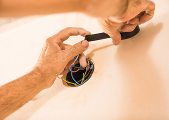 man working with electrical tape on wires