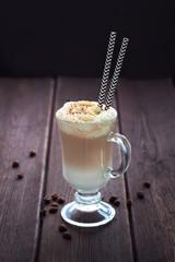 Latte Macchiato with whipped cream on dark wooden background