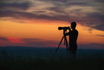 The man use the camera against the background of sunset