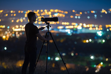The man work with a camera on the background of night city light. Wide angle