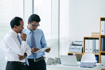 Business people discussing information on tablet computer