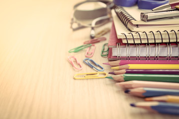 School supplies on wooden table in vintage color tone