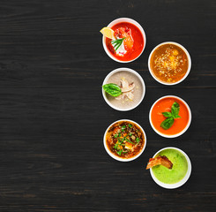 Six soups at black wood, top view with copy space