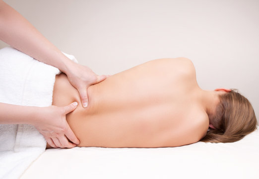 Deep tissue massage on the woman's lower back on quadratus lumborum muscle
