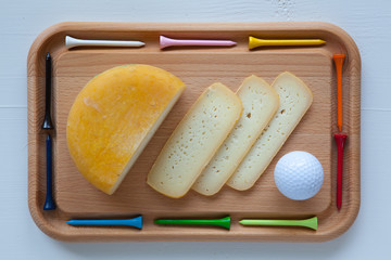 Block of tasty cheese on cutting board with a knife and golf tee