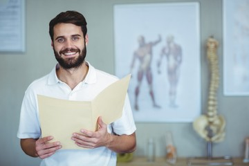 Portrait of physiotherapist holding file