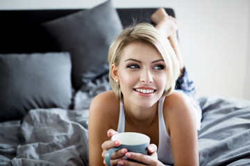 Smiling woman drinking a coffee lying in bed.