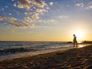 Woman walking the beach in sunset