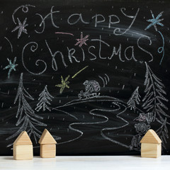 fairytale Christmas night in the village/ Wooden houses on the background of a winter landscape painted by with chalk on blackboard