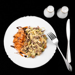 Salad with meat, carrot, mushrooms, eggs and mayonnaise on black background