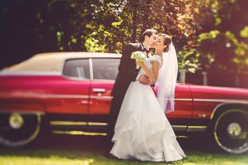 Groom hugs bride's waist kissing her in a cheek before old red D
