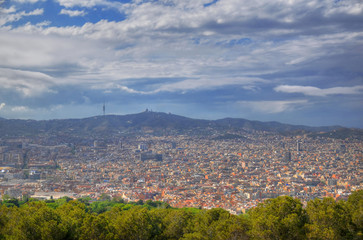 Panoramic aerial view of Barcelona city in Spain from the Montjuic Castle - Colorful HDR image on a partially cloudy day