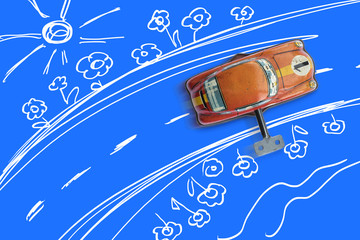 Old toy car running on a road drawn by children