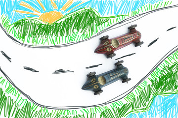 Old toy cars running on a road drawn by children