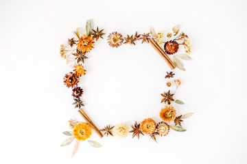 dry flowers, cinnamon and cardamom round frame wreath pattern on white background. flat lay, top view