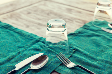 close up of cutlery with glass and napkin on table