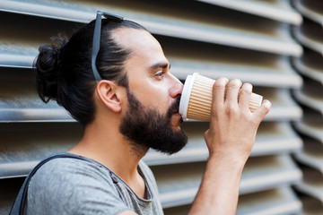 man drinking coffee from paper cup on street