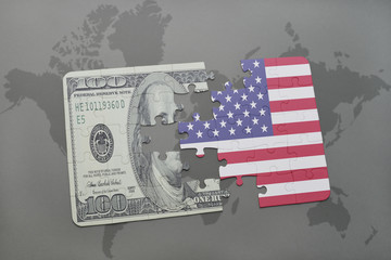 puzzle with the national flag of united states of america and dollar banknote on a world map background.