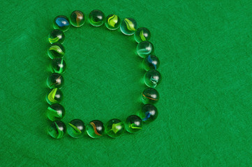 The letter D made out of marbles on a green background