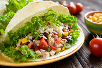 Mexican tacos with meat, beans, lettuce, corn, onion, tomato and
