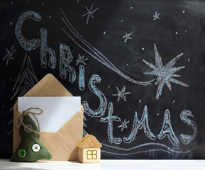 in anticipation of holiday/ festive Christmas tree and a toy house with an open envelope on the background of the inscription Merry Christmas done in chalk on a blackboard