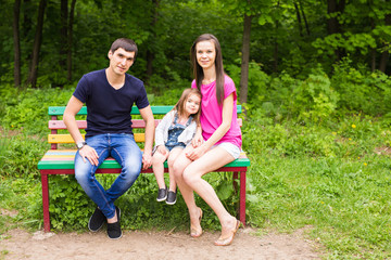 young family sitting on a bench in the summer park