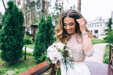 beautiful bride with white bouquet in park