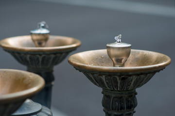 Close up on one faucet on a Benson Bubbler water fountain in Portland, Oregon