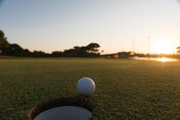 golf ball on edge of  the hole