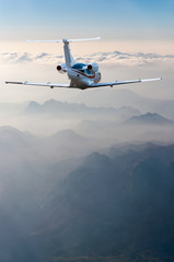 perspective view of jet airliner in flight with mountains background