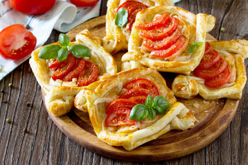 Cakes with red fish (salmon and puff pastry) and tomatoes on a w
