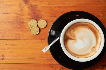 cup of coffee on the table and coins