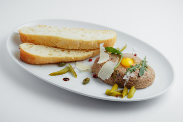 Meat cutlet with pickled cucumbers, fresh herbs and bread on a white plate