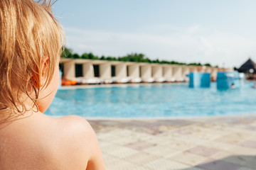 Child looking at the swimming pool