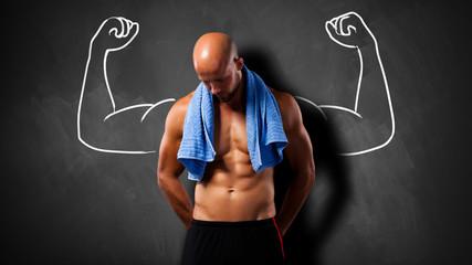 Muskulöser Mann vor einer Kreidetafel mit Kraftgeste