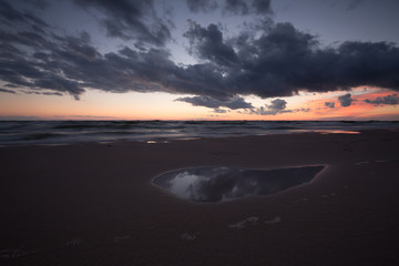Sunset at the beach with the clouds reflecting in a pool of water