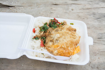 Basil fried rice with chicken and fried egg in white foam box.