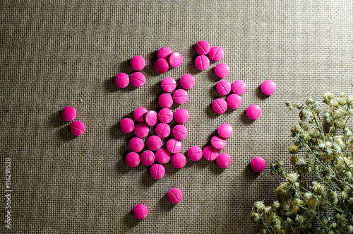 pink or purple pill isolate on wood background stock photo and