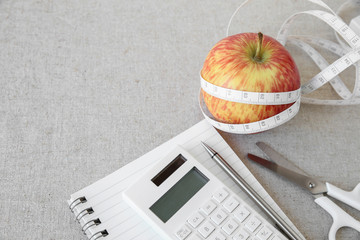 Apple, tape measure, notebook and calculator background for diet