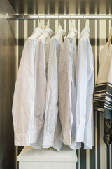 Row of white shirts hanging in retro style background wardrobe