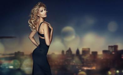 Blond model with long hair posing in black dress Wall mural