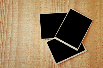 top view of blank photos frame on wooden background