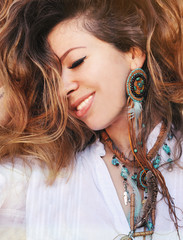 Beauty close up fashion smiling woman portrait with handmade necklace and earrings made with beads, leather and feathers, boho chic style, perfect skin and volume curly hairstyle, outdoor photo
