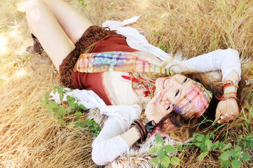 Dressed in boho chic style woman lying on a hay, sunny day outdoor