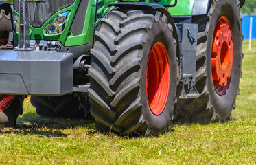 Wall Mural - Powerful tractor wheels go over the ground up dust