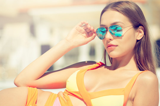 Beautiful woman in sunglasses have sunbath and relaxing near poo