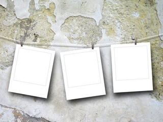 Close-up of three blank square instant photo frames hanged by pegs against scratched concrete wall background