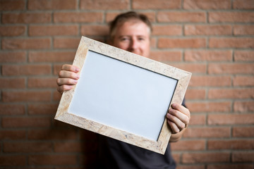 man holds a white wooden frame with blank space, brick wall background - free space for adding custom text or image