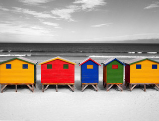 The row of wooden brightly colored huts on Sunrise Beach. Atlantic ocean. Muizenberg, South Africa. Black and white image with colored parts. Artistic retouching.