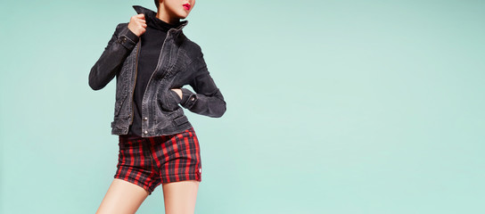 Wall Mural - Woman with jeans jacket with red plaid short pants isolated on pastel green background. with copy space.